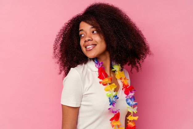 Young african american woman wearing a hawaiian stuff looks aside smiling, cheerful and pleasant.