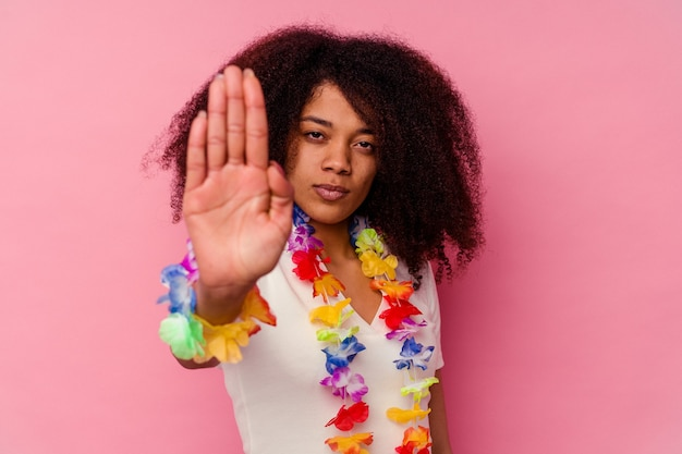 Young african american woman wearing a hawaiian stuff standing with outstretched hand showing stop sign, preventing you.