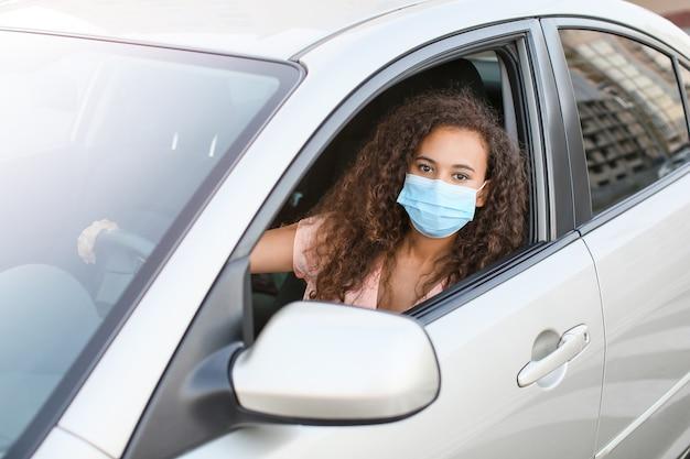 차에 앉아있는 동안 의료 마스크를 쓰고 젊은 아프리카 계 미국인 여자