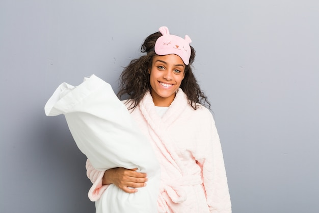 Young african american woman wearing a pajamas and a sleep mask holding a pillow happy, smiling and cheerful.