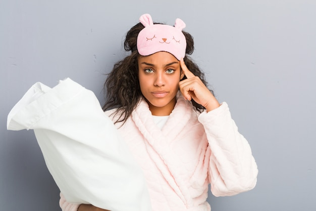 Young african american woman wearing a pajamas and a sleep mask holding a pillow pointing his temple with finger, thinking, focused on a task.