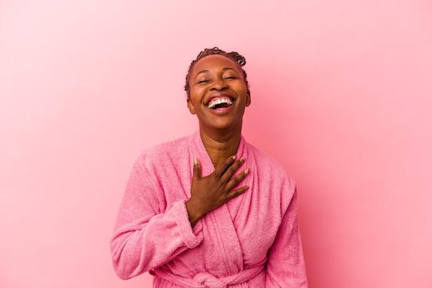 Молодая афро-американская женщина в розовом халате, изолированном на розовом фоне, громко смеется, держа руку на груди.