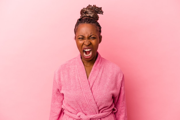 ピンクの背景に分離されたピンクのバスローブを着た若いアフリカ系アメリカ人女性は、非常に怒って攻撃的に叫んでいます。