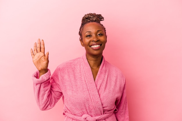 Young african american woman wearing pink bathrobe isolated on pink background smiling cheerful showing number five with fingers.