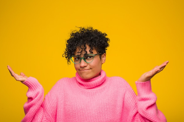 Young african american woman wearing a pink sweater doubting and shrugging shoulders in questioning gesture.