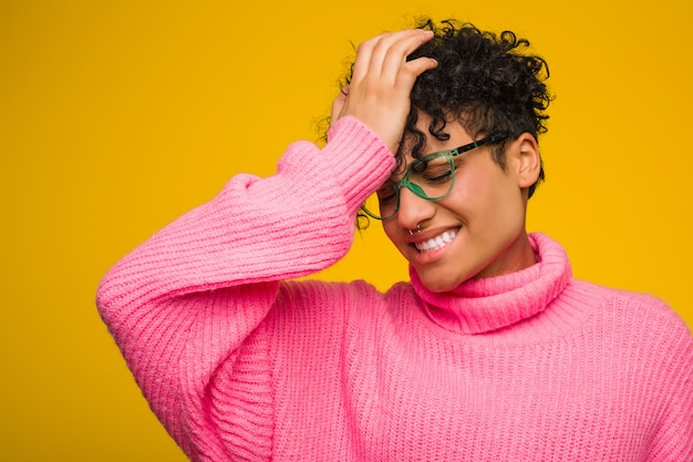 Young african american woman wearing a pink sweater forgetting something, slapping forehead with palm and closing eyes.