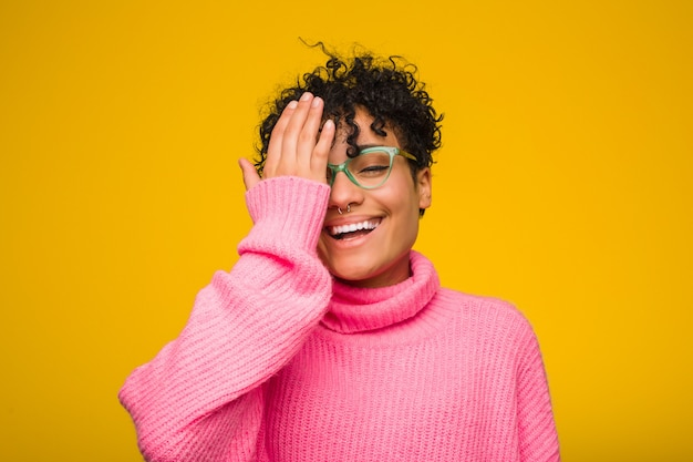 Young african american woman wearing a pink sweater having fun covering half of face with palm.
