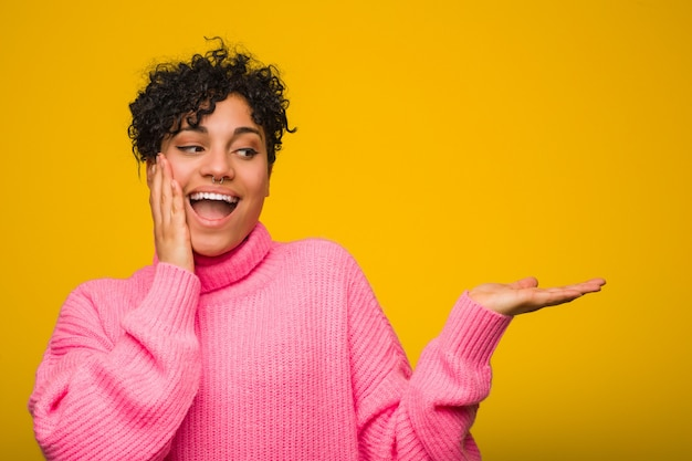 Young african american woman wearing a pink sweater holds copy space on a palm, keep hand over cheek. amazed and delighted.