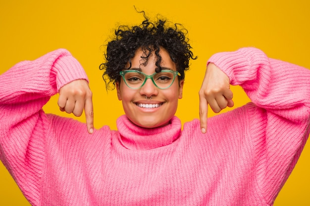 Young african american woman wearing a pink sweater points down with fingers, positive feeling.