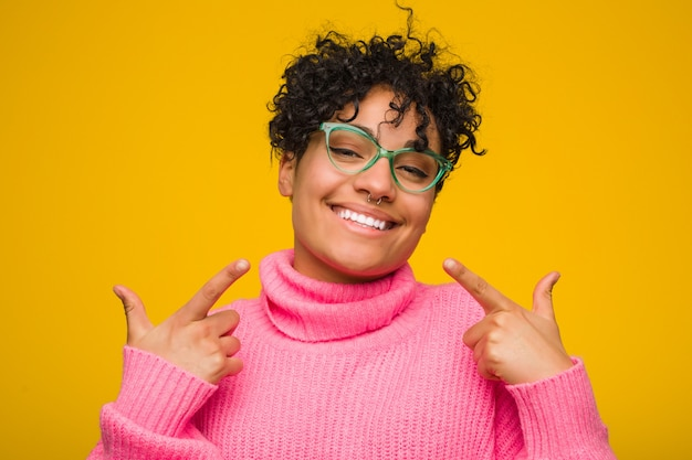 Young african american woman wearing a pink sweater smiles, pointing fingers at mouth.