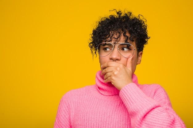 Young african american woman wearing a pink sweater thoughtful  to a  covering mouth with hand.