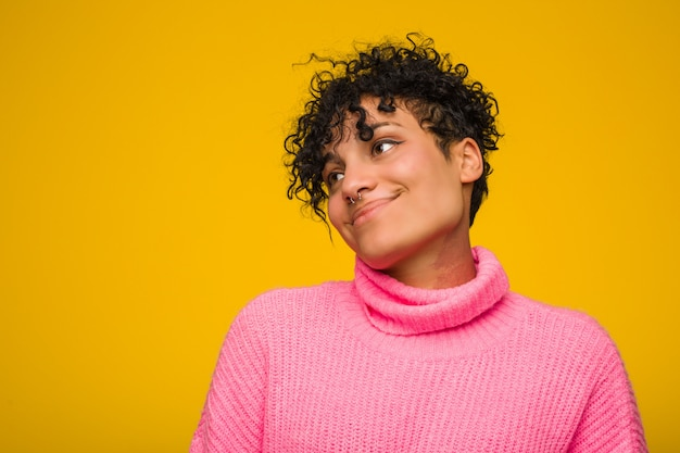 Young african american woman wearing a pink sweater touches tummy, smiles gently, eating and satisfaction concept.