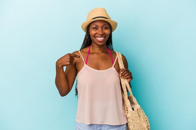 誇りと自信を持って、シャツのコピースペースを手で指している青い背景の人に分離された夏服を着ている若いアフリカ系アメリカ人女性