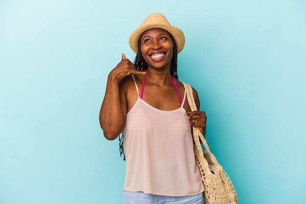 指で携帯電話の呼び出しジェスチャーを示す青い背景で隔離の夏服を着ている若いアフリカ系アメリカ人の女性。