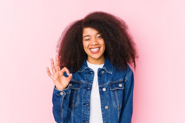 젊은 아프리카 계 미국인 여자는 눈을 윙크하고 손으로 괜찮아 제스처를 보유하고 있습니다.