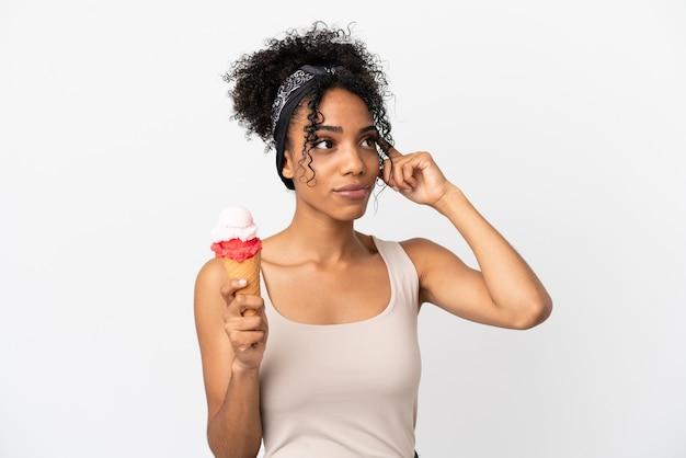 Молодая афро-американская женщина с мороженым корнет, изолированные на белом фоне, сомневаясь и думая