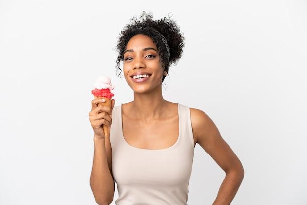 Молодая афро-американская женщина с мороженым корнет, изолированные на белом фоне, позирует с руками на бедре и улыбается