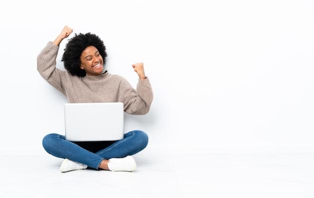 Молодая афро-американских женщина с ноутбуком, сидя на полу, празднует победу