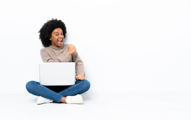 勝利を祝って床に座ってラップトップを持つ若いアフリカ系アメリカ人女性