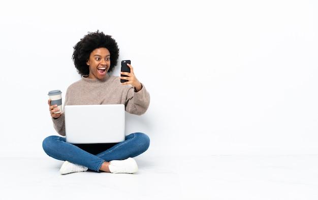 奪うコーヒーと携帯電話を保持している床に座ってラップトップを持つ若いアフリカ系アメリカ人女性