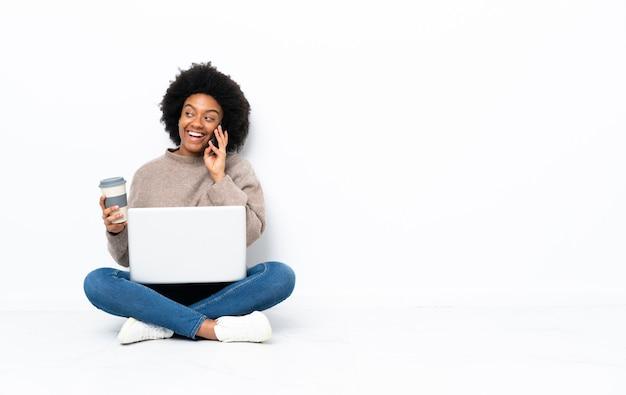 Молодая афроамериканская женщина с ноутбуком сидит на полу, держа кофе на вынос и мобильный