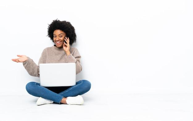Молодая афроамериканская женщина с ноутбуком сидит на полу и разговаривает с кем-то по мобильному телефону