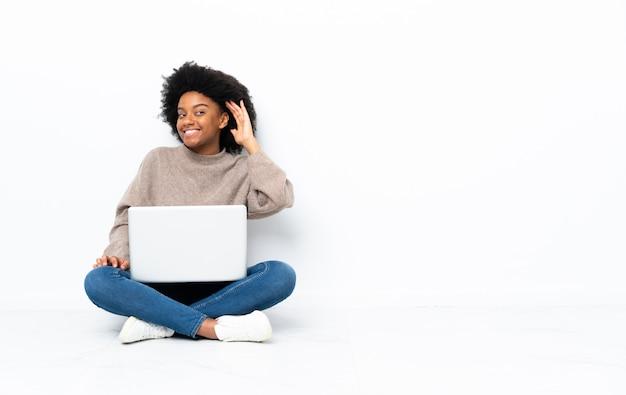 귀에 손을 넣어 뭔가를 듣고 바닥에 앉아 노트북과 젊은 아프리카 계 미국인 여자