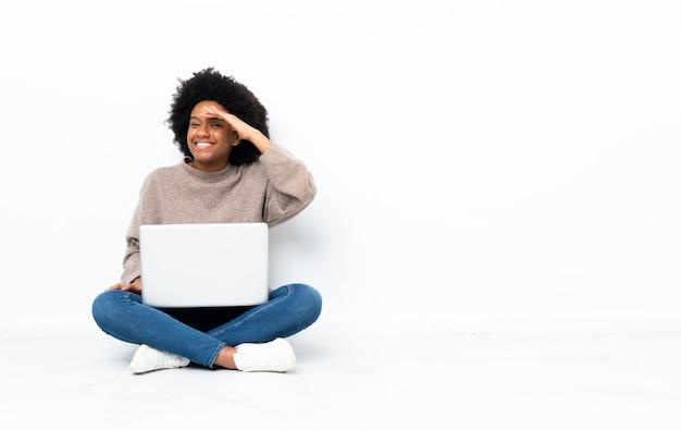 何かを見て手で遠くを見て床に座ってラップトップを持つ若いアフリカ系アメリカ人女性