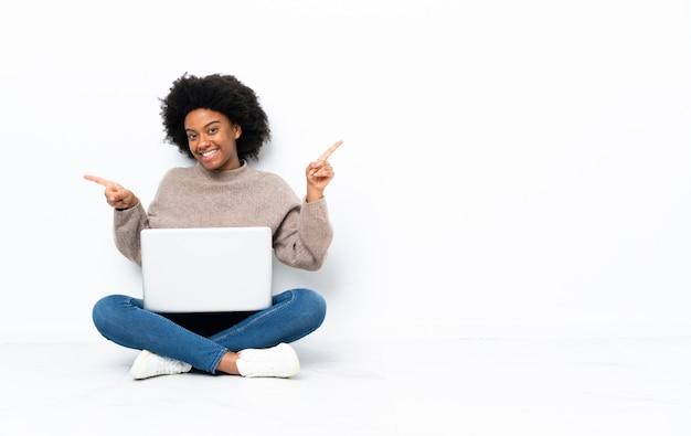 Молодая афроамериканец женщина с ноутбуком, сидя на полу, указывая пальцем на боковых и счастливым