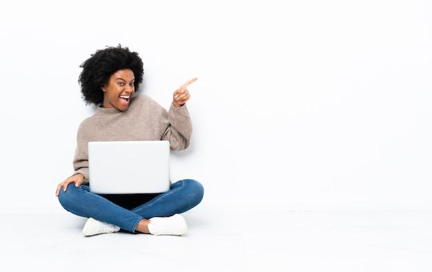 Молодая афроамериканская женщина с ноутбуком сидит на полу, указывая пальцем в сторону и представляя продукт