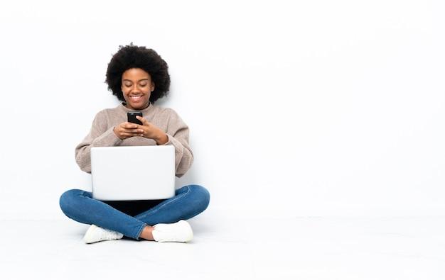 Молодая афроамериканская женщина с ноутбуком сидит на полу, отправляя сообщение с мобильного телефона