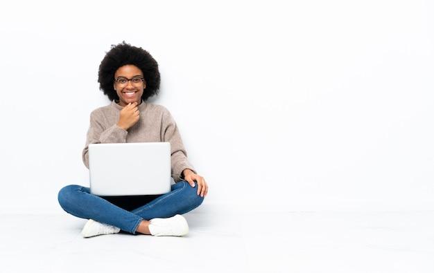 Молодая афро-американских женщина с ноутбуком, сидя на полу в очках и улыбается