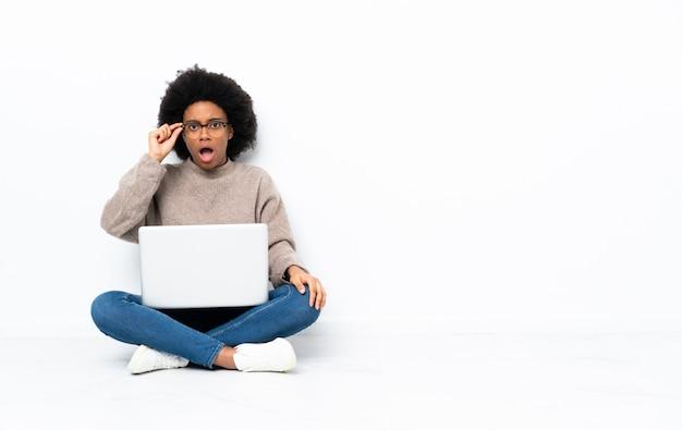 Молодая женщина афроамериканцев с ноутбуком, сидя на полу в очках и удивлен