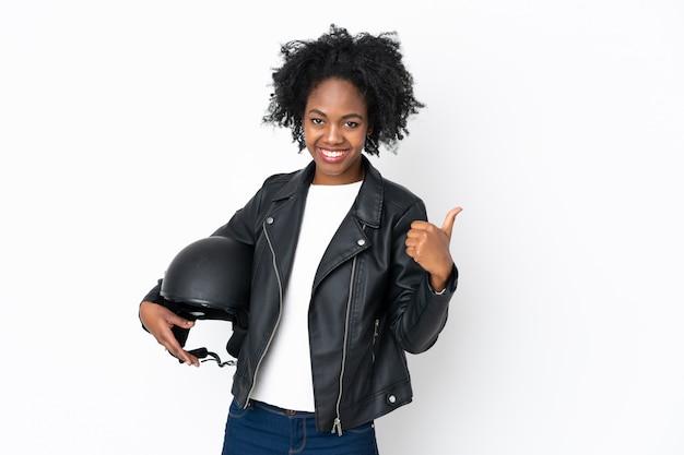 親指のジェスチャーを与える白い壁にオートバイのヘルメットを持つ若いアフリカ系アメリカ人女性