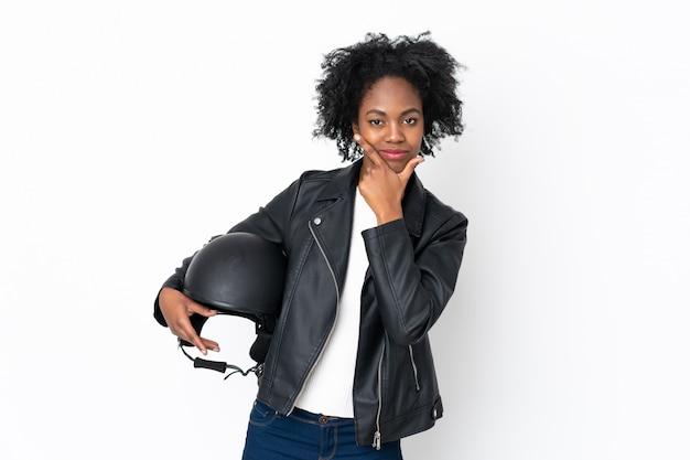 Молодая афро-американская женщина с шлемом мотоцикла на белой стене думая идея