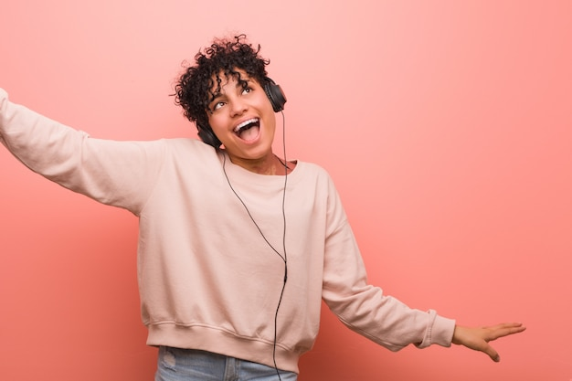 Young african american woman with a birthmark dancing and listening to music with a headphone