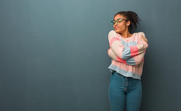 抱擁を与える青い目を持つ若いアフリカ系アメリカ人女性