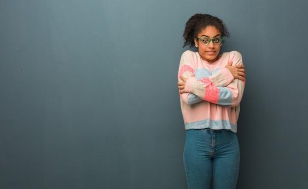 Молодая женщина афроамериканца с голубыми глазами становится холодно из-за низкой температуры