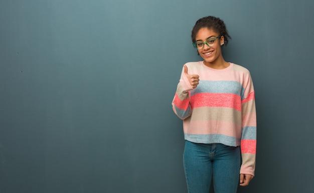 笑顔と親指を上げて青い目をした若いアフリカ系アメリカ人女性