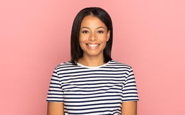 ピンクの壁に陽気で満足している陽気な笑顔の幸せな女の子と若いアフリカ系アメリカ人の女性