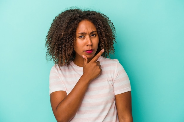 Young african american woman with curly hair isolated on blue background contemplating, planning a strategy, thinking about the way of a business.