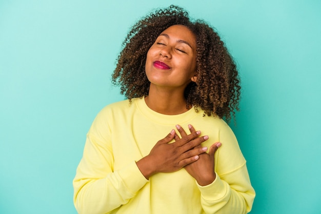 Young african american woman with curly hair isolated on blue background has friendly expression, pressing palm to chest. love concept.