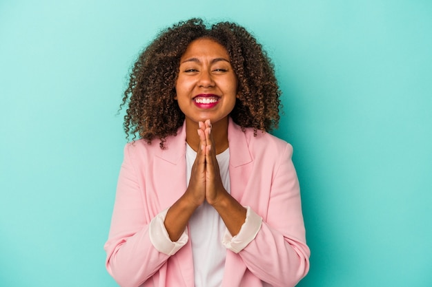 Young african american woman with curly hair isolated on blue background holding hands in pray near mouth, feels confident.