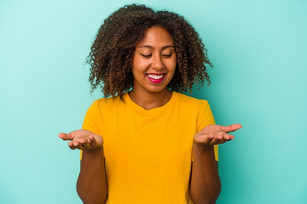Young african american woman with curly hair isolated on blue background holding something with palms, offering to camera.