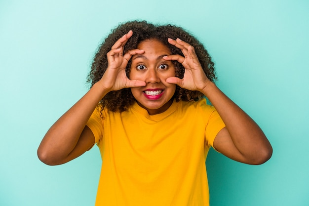 Young african american woman with curly hair isolated on blue background keeping eyes opened to find a success opportunity.