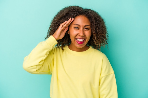 Young african american woman with curly hair isolated on blue background shouts loud, keeps eyes opened and hands tense.