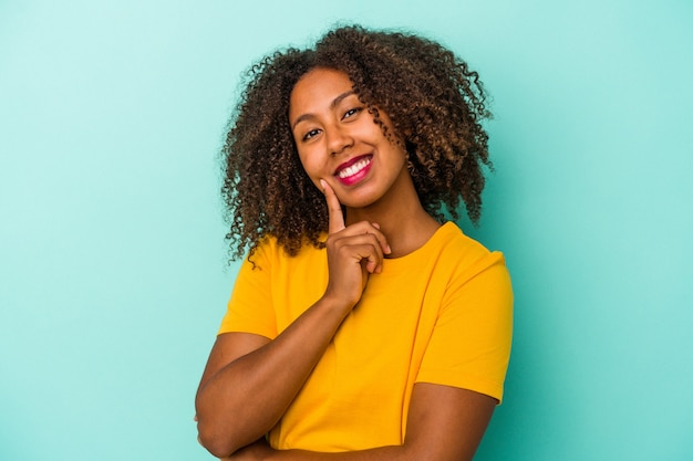 Young african american woman with curly hair isolated on blue background smiling happy and confident, touching chin with hand.