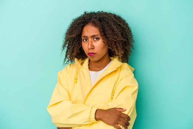 Young african american woman with curly hair isolated on blue background suspicious, uncertain, examining you.
