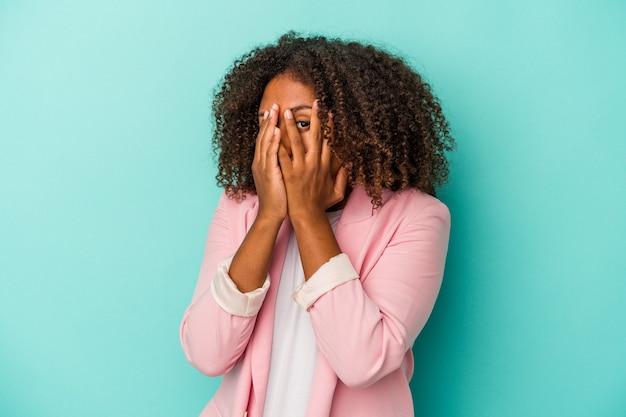 青い背景に分離された巻き毛を持つ若いアフリカ系アメリカ人の女性は、おびえ、神経質な指を点滅します。