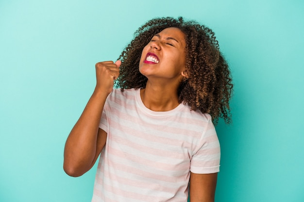 勝利、情熱と熱意、幸せな表現を祝う青い背景に分離された巻き毛の若いアフリカ系アメリカ人女性。